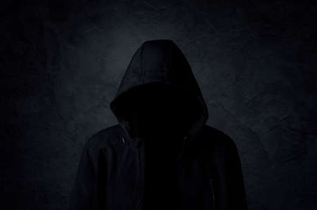 Hooded man over dark concrete background Archivio Fotografico