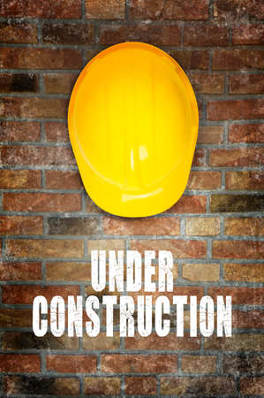 website words: Under construction. Yellow safety helmet on brick wall background. Stock Photo