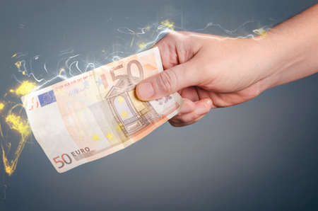 expenses: Male hand holding a burning fifty euro banknote. Fire illustration. Stock Photo