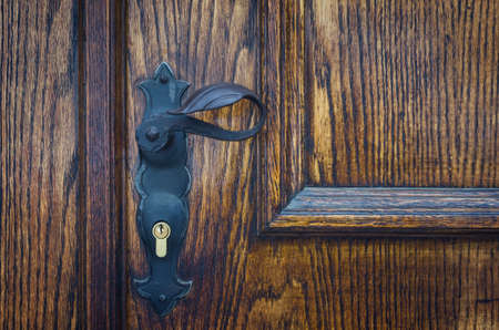 Close up of an old wooden door with metal handle