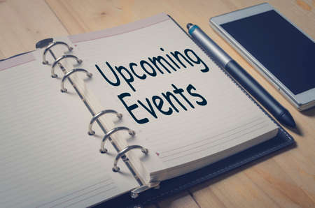Concept Upcoming Events message on notebook with pen and smart phone on wooden table