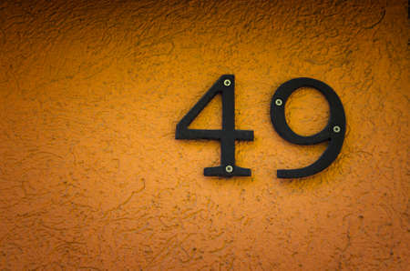 four objects: House number forty nine (49) on orange concrete wall