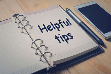 advice: Helpful tips message on notebook with pen and smart phone on wooden table