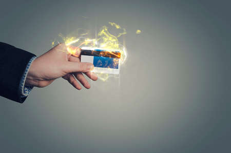 excess: Businessman`s hand with burning bank credit plastic card. Fire illustration.