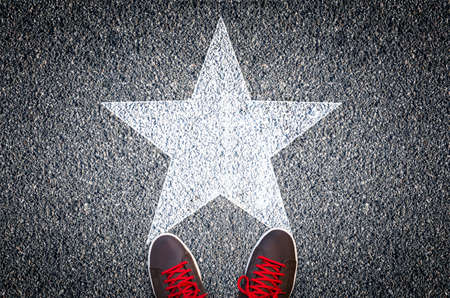 Sneakers on asphalt road with white star