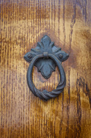 Iron knocker on old wooden door