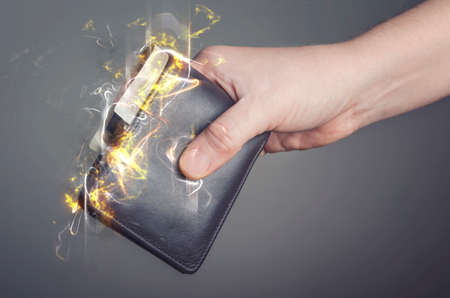 Male hand holding a burning wallet. Fire illustration. Stock Photo