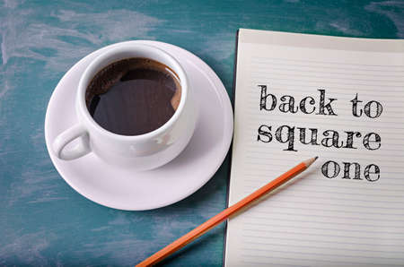 Back to square one text in a notebook with pencil and coffee cup