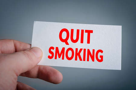 quiting smoking: Quit smoking card in hand with dark background