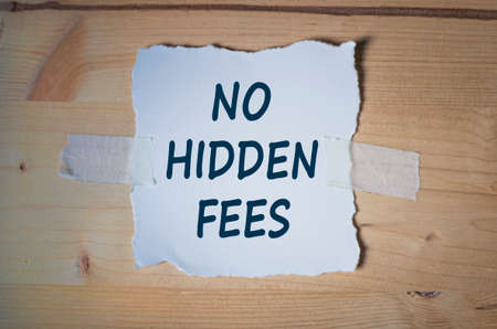 hidden fees: Torn paper note on wooden board. No Hidden Fees Message. Vintage toned conceptual image.
