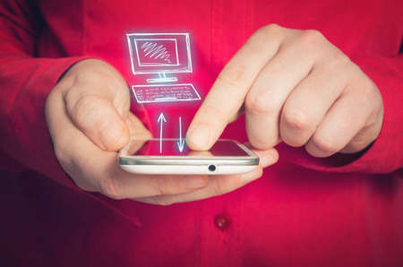 navigating: Man synchronizing his mobile and desktop in a conceptual image with a hand-drawn icon for the desktop, closeup view of his hands navigating the touch screen of the phone.