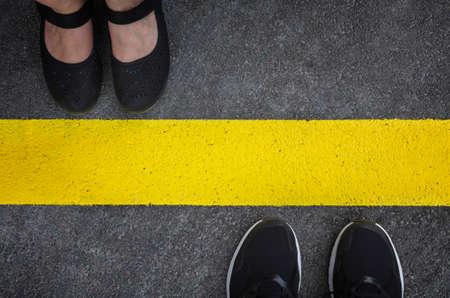 カップルに立って黄色アスファルト行トップ ビューで割った互いに反対の足 写真素材