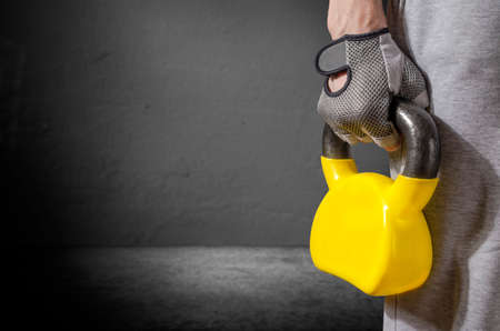 Cropped image of young man in sweatpants holding kettle bell Stock Photo