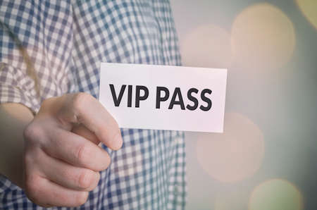 Vip pass in hand with bokeh lights background Stock Photo