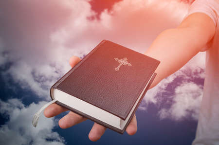 Hand with Holy Bible book and cloud background. Freedom of religion concept. Stock Photo