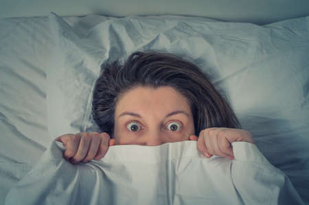 Scared young woman lying in bed and hiding under the sheet
