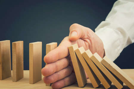 사업가 떨어지는와 직립 나무 블록 사이에 손을 삽입 도미노 효과를 중단 스톡 콘텐츠