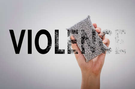 Hand erasing the word VIOLENCE