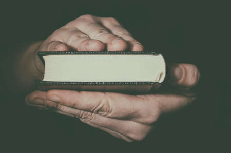 Holy Bible in man`s hands closeup. Low key image. Stock Photo - 85943689