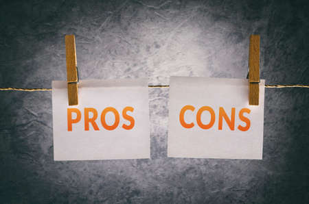 questions: Pros and cons paper note attach to rope with clothes pins on dark background
