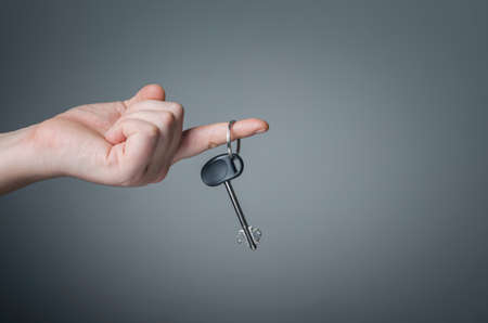 Hand giving house key on dark background