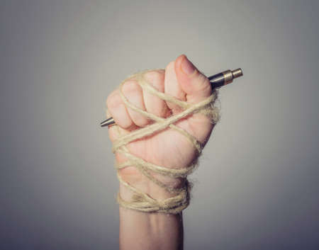 Hand with pen tied with rope, depicting the idea of freedom of the press or freedom of expression Reklamní fotografie