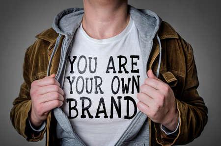 Człowiek, który pokazuje swoją własną markę na t-shirt. Koncepcja osobistego brandingu.