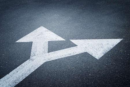 Ein bidirektionales Pfeilsymbol auf einer Asphaltstraße für das Konzept der Wahl
