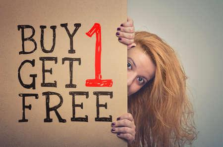 Woman with long hair peeking behind a Buy 1 Get 1 Free billboard poster.