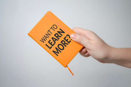 Want to learn more? notebook in hand. Education concept.
