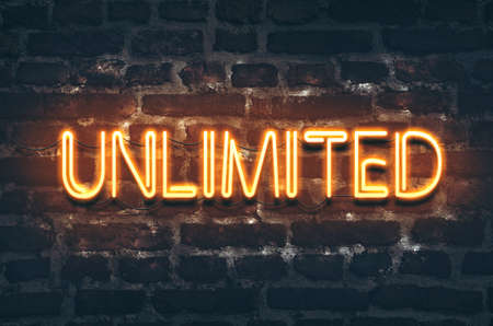 Unlimited neon sign on dark brick wall background Stock Photo