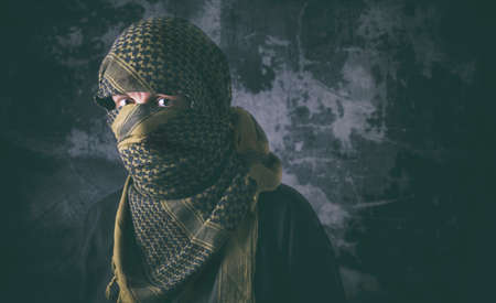 Masked terrorist with tactical Shemagh scarf and treating look with grungy background. Concept of terrorism and violence.