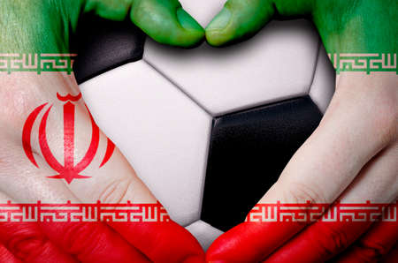 Hands painted with an Iran flag forming a heart over soccer ball background Foto de archivo