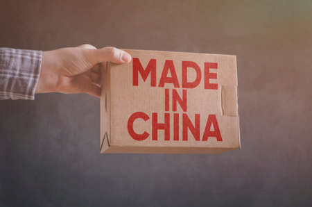 Man`s hand with carton box with Made in China label imprint