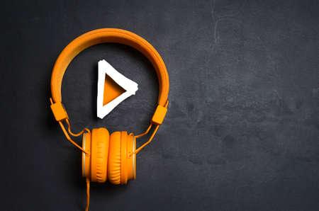 Botón de reproducción y auriculares naranja sobre fondo de hormigón oscuro