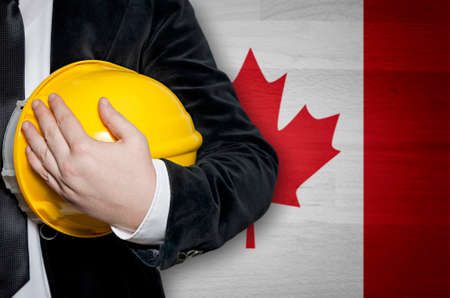 Engineer with yellow plastic helmet on a Canadian flag background