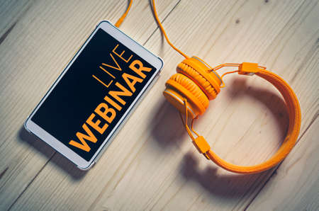 Live webinar on tablet with headphones on wooden table background. E-learning concept.