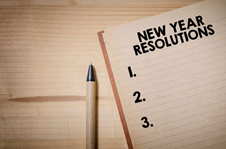 New Year Resolutions checklist on notebook on a wooden table Stock Photo