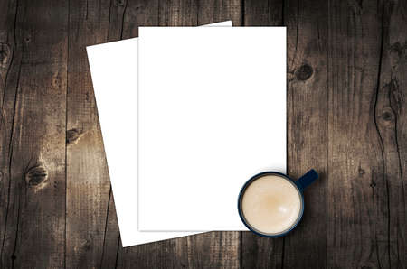 Blank letterhead and coffee cup on vintage wooden table background. Stock Photo