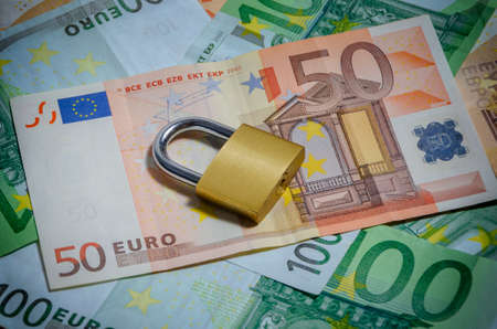 Lock on Euro banknotes background - concept of saving money Stock Photo