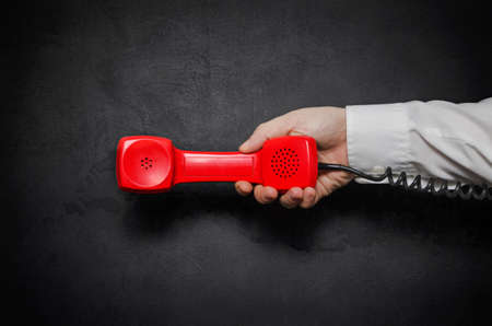 Hand with red old fashioned style telephone handset receiver
