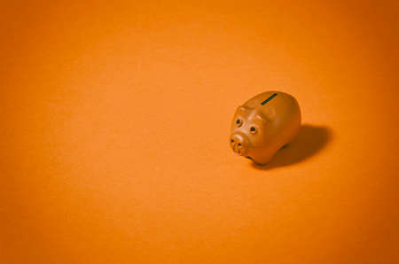 Piggy coin bank on orange background. Money savings and financial security concept. Stock Photo