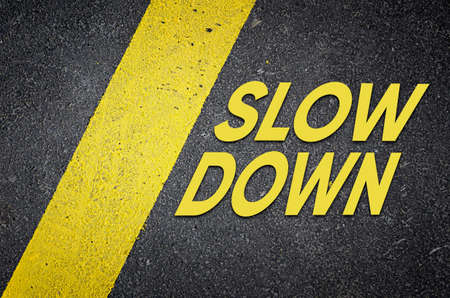 Asphalt road with text slow down near yellow line. Traffic safety concept. Stock Photo