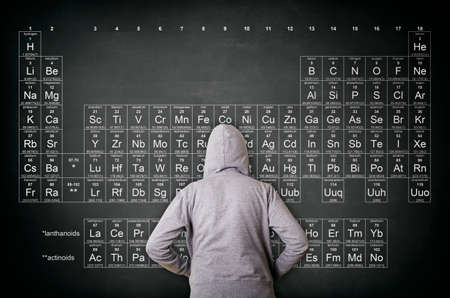 Rear view of hooded man against blackboard with periodic table of elements. Education and science concept.