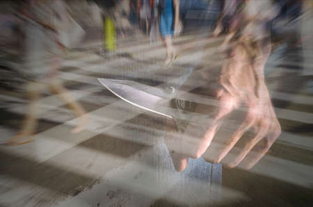 Terrorist is attacking with a knife in a public place. Stock Photo