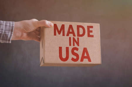 The man`s hand with carton box with Made in USA label imprint