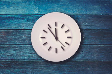 Clock on the plate on blue wooden background Stock Photo