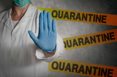 Health worker gesturing stop sign in quarantine.