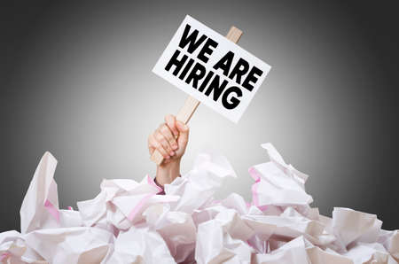 We are hiring placard in hand with crumpled paper pile. Search for worker, employee concept.