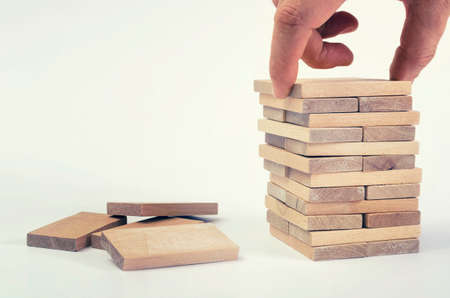 Businessman`s hand placing block on wooden tower. Business development concept.